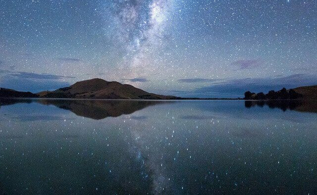 Starry night sky over a lake