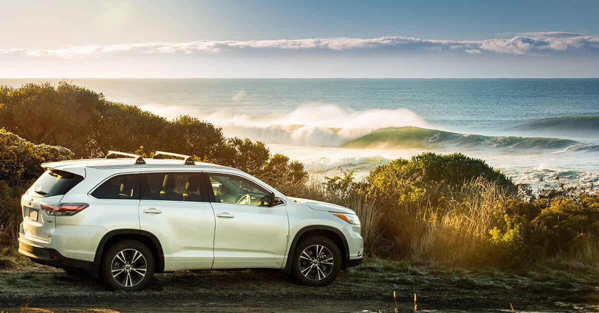 Image of a Toyota Highlander parked up next to the beach